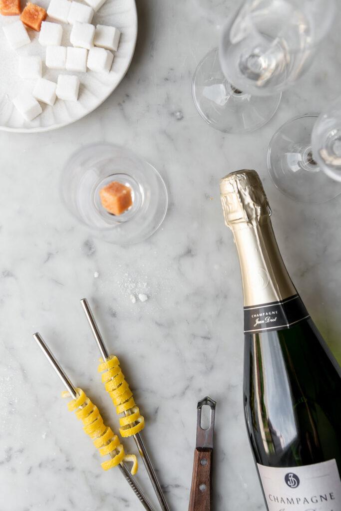 sugar cubes, angostura bitters, lemon twist, champagne, flutes