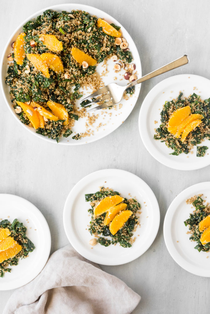 quinoa kale salad with citrus tahini dressing and orange wedges