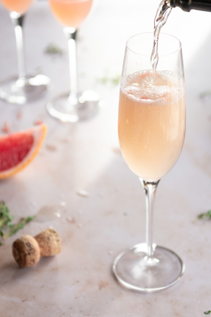 topping grapefruit mimosa with prosecco