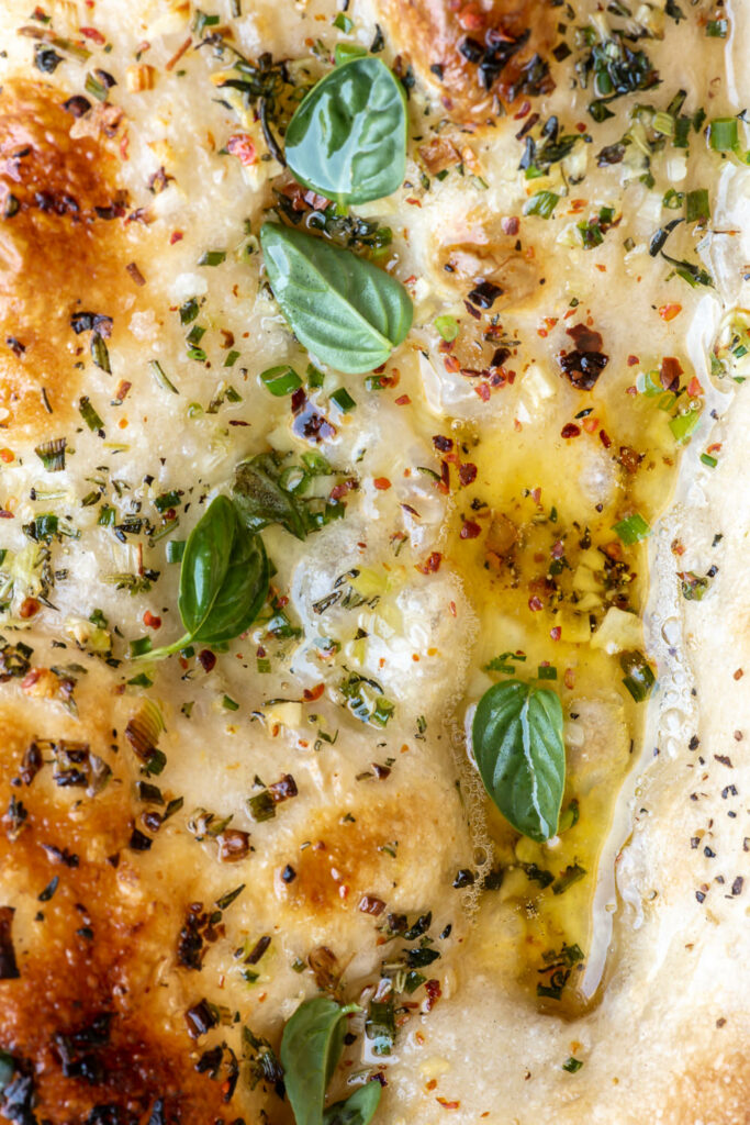 pizza with pools of garlic butter and herbs